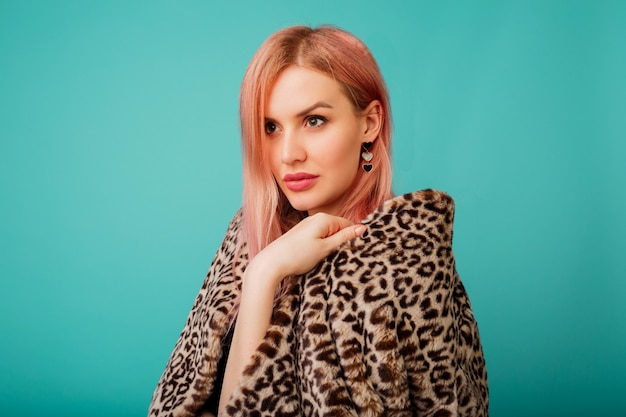 Portrait of stunning woman with pink hair in stylish winter fluffy coat with leopard print