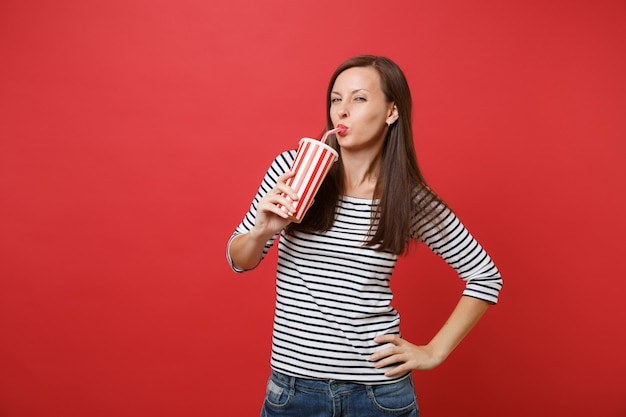 Portrait of stunning young woman in casual striped clothes drinking cola or soda from plastic cup isolated on bright red wall background. people sincere emotions lifestyle concept. mock up copy space.