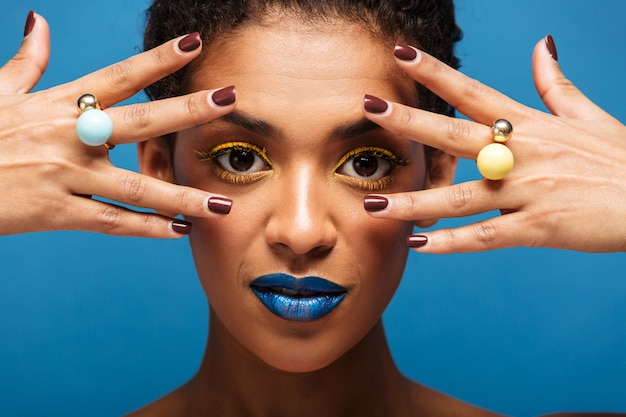 Portrait of stylish adorable afro woman with colorful makeup demonstrating rings on her fingers keeping hands at face, isolated over blue wall