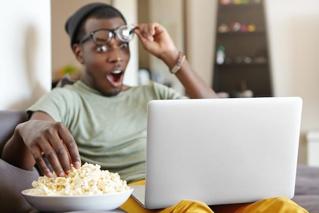 Ritratto di uomo afro-americano alla moda con il computer portatile a casa