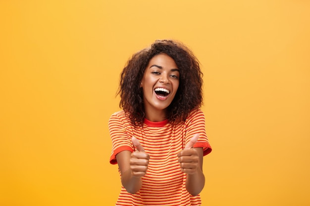 Portrait of stylish african american woman with curly hairstyle showing thumbs up.