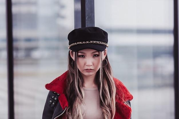 街の通りでポーズをとってカメラを見て赤い毛皮の帽子とジャケットを身に着けている肖像画のスタイリッシュなアジアの女の子