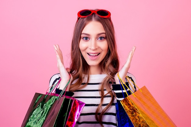 Portrait of a stylish and attractive crazy shopaholic woman in striped sweater holding a lot of shopping bags surprised and shocked on a pink background in the studio. concept of shopaholism and sale