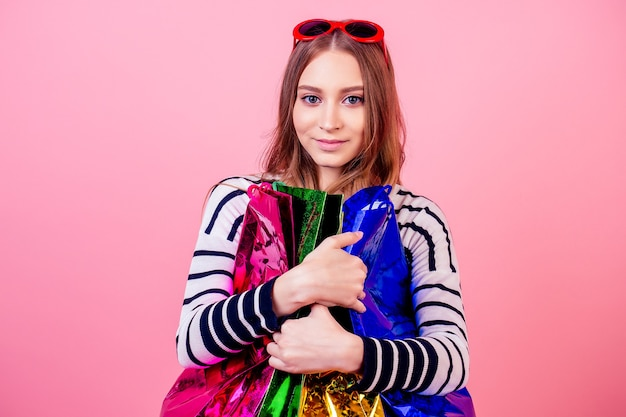 Portrait of a stylish and attractive female person in a striped sweater and red sunglasses smiling and hugs a lot of shopping bags on a pink background in the studio. concept of shopaholism and sales