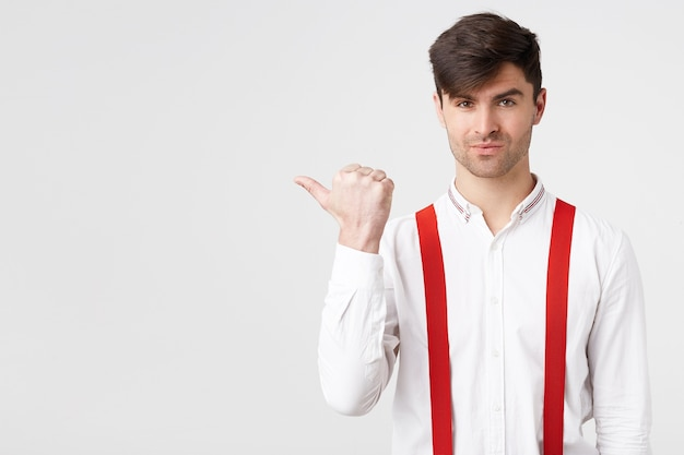 Portrait of stylish attractive guy in white shirt and red suspender pointing aside with flirting charming facial expression