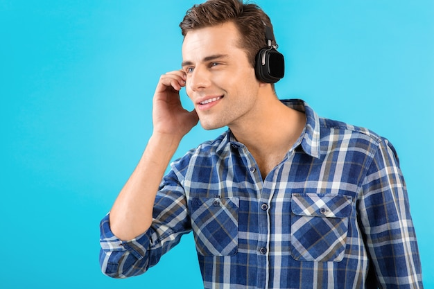 Portrait of stylish attractive handsome young man listening to music on wireless headphones having fun modern style happy emotional mood