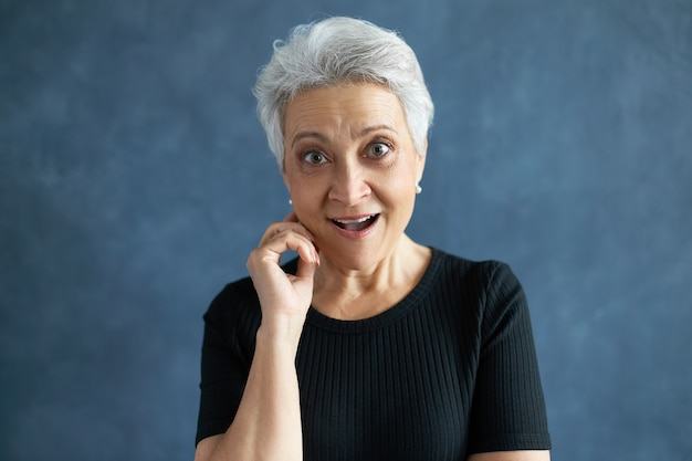 Portrait of stylish attractive retired female with gray hair opening mouth widely exclaiming excitedly, expressing amazement, being surprised with unexpected news, holding hand at her face