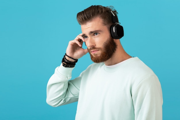 Portrait of stylish attractive young bearded man listening to music on wireless headphones modern style confident mood