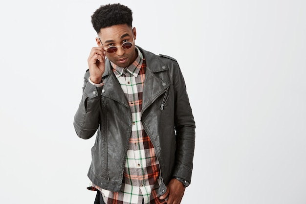 Ritratto di giovane modello maschio africano dalla pelle scura attraente alla moda con capelli ricci in outwear di cuoio nero che toglie gli occhiali da sole con la mano con l'espressione fresca e calma.