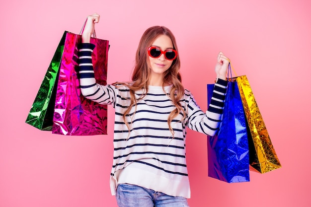 Portrait of a stylish and attractive young girl in a striped sweater and red sunglasses smiling and holding a lot of shopping bags on a pink background in the studio. concept of shopaholism and sales
