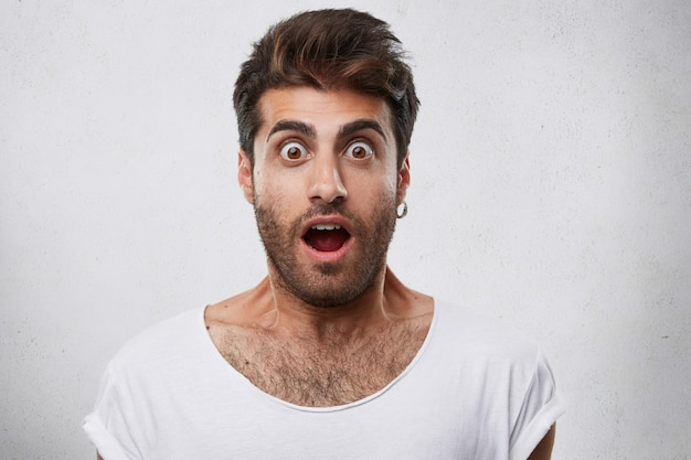 Portrait of stylish bearded guy having trendy hairstyle wearing earring and white t-shirt looking with his eyes popped out and opened mouth having shock and scared look.