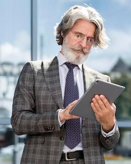 Ritratto di uomo barbuto alla moda che tiene compressa