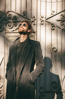 Portrait of a stylish bearded man in sunglasses and coat