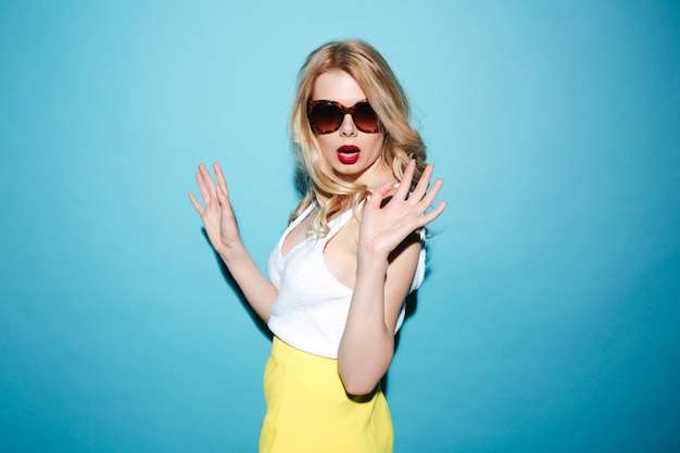 Portrait of a stylish blonde woman wearing sunglasses and posing