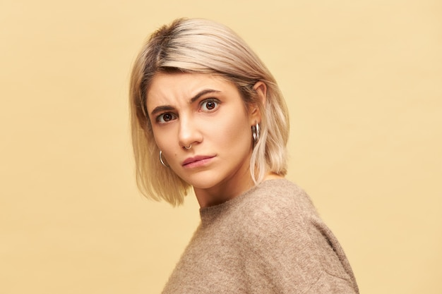 Portrait of stylish blonde young woman wearing cozy sweater staring in indignation, frowning eyebrows, being disgusted with bad smell, stink. indignant girl expressing displeasure