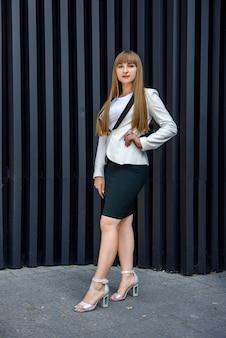 Portrait of stylish business woman near grey wall background