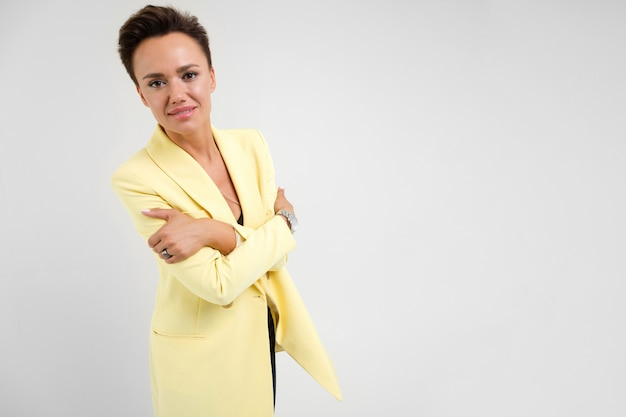 Portrait of a stylish business woman on a white surface in a lemon jacket