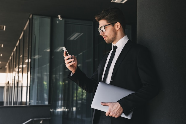 Portrait of stylish businessman dressed in formal suit standing outside glass building with laptop, and using mobile phone