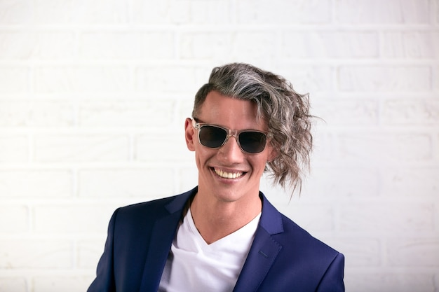 Portrait of stylish businessman with curly long hair in sunglasses smiling at the camera on white background