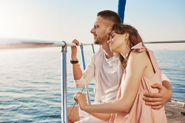 Portrait of stylish couple in love, hugging while sitting on bow of private yacht and enjoying view of sea. husband took his wife to beautiful warm country, celebrating honeymoon