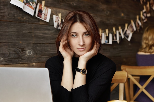 Portrait of stylish cute brunette girl wearing wrist watch sitting in front of laptop, browsing internet, using free wireless connection at modern restaurant, waiting for friend to join her for lunch