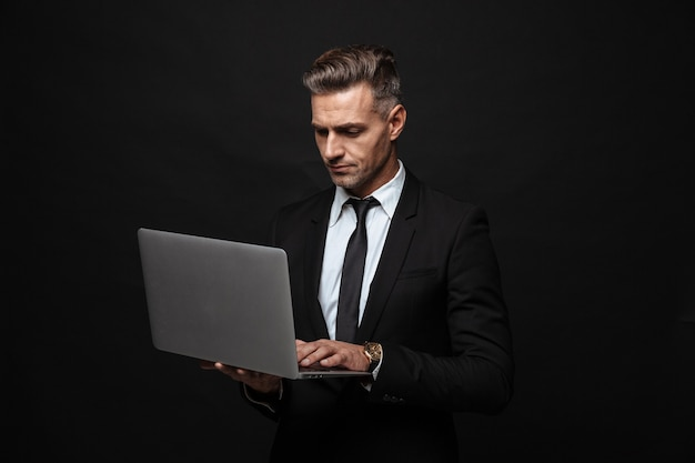 Portrait of stylish european businessman dressed in formal suit using and looking at laptop computer isolated over black wall