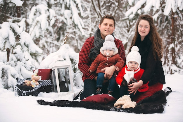 Portrait of a stylish family having a good time in the winter forest. decorated place to relax.