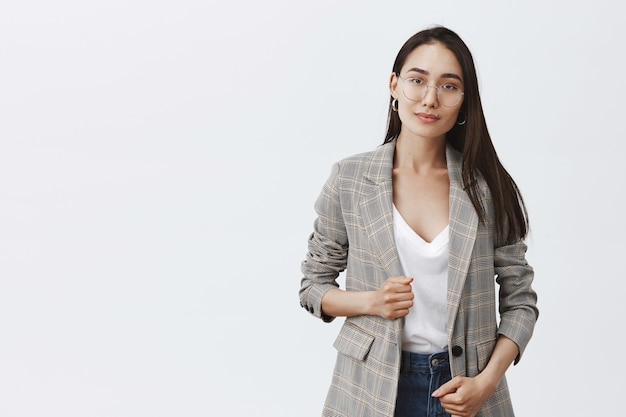 Ritratto di donna alla moda femminile in giacca e occhiali alla moda, sorridente educatamente e in piedi sopra il muro grigio