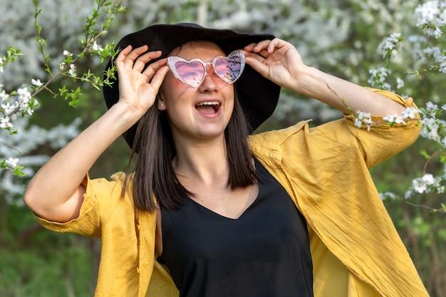 Ritratto di una ragazza alla moda tra alberi in fiore nella foresta.