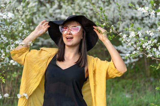 Ritratto di una ragazza alla moda tra alberi in fiore nella foresta