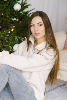 Portrait of a stylish girl with long hair and nude makeup near the christmas tree