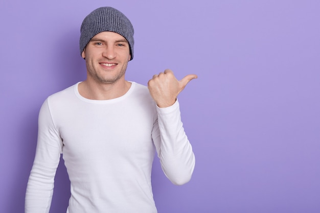 Portrait of stylish handsome young man osing isolated on lilac. male smiling and points aside, wears white casual long sleeve shirt and gray cap. copy space for advertisment or promotion.