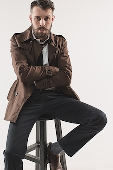 Portrait of stylish handsome young man sitting at studio against white. man wearing jacket
