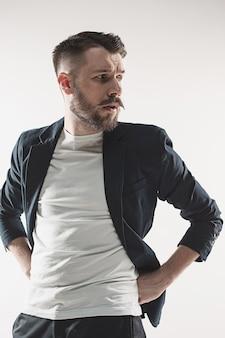 Ritratto del giovane bello alla moda che sta allo studio contro il bianco. uomo che indossa una giacca