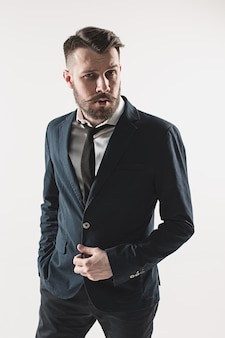 Portrait of stylish handsome young man standing at studio against white. man wearing jacket