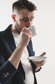 Ritratto del giovane bello alla moda che sta allo studio. uomo che indossa giacca e azienda tazza di caffè
