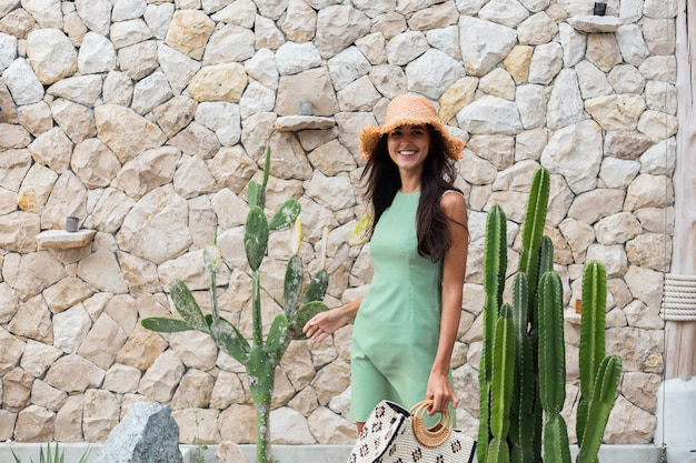 Portrait of stylish happy cute smiling woman in elegant summer green dress holding bag wearing straw hat on background of white stone wall and cactus