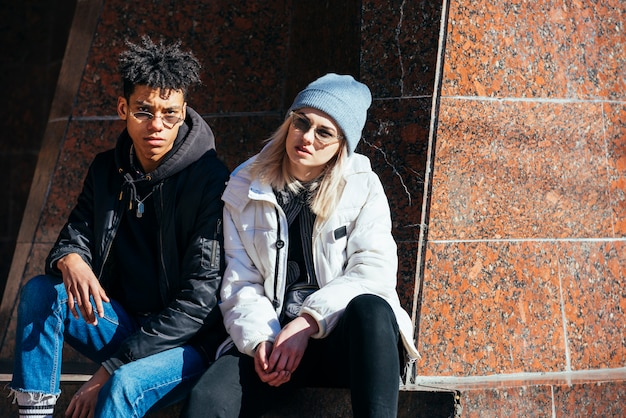 Portrait of stylish interracial young couple looking at camera