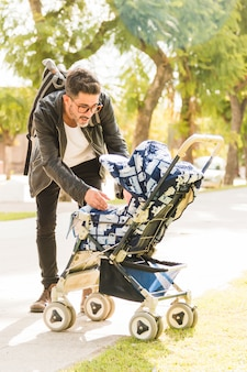 Portrait of stylish man carrying her baby from stroller in the park