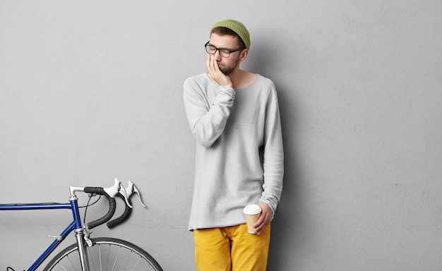 Portrait of stylish man keeping takeaway hot coffee, looking sad while having toothache, standing near bike, going to ride to university. young male hipster in fashionable clothes feeling pain