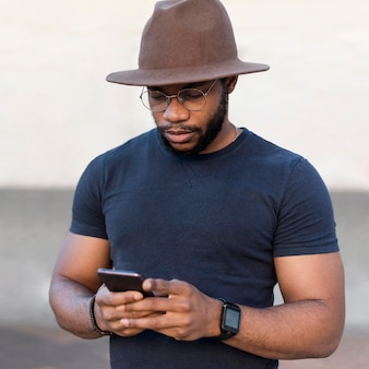 Portrait of stylish man looking on his phone