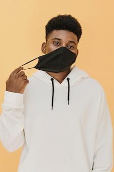 Ritratto dell'uomo alla moda che toglie la sua maschera facciale