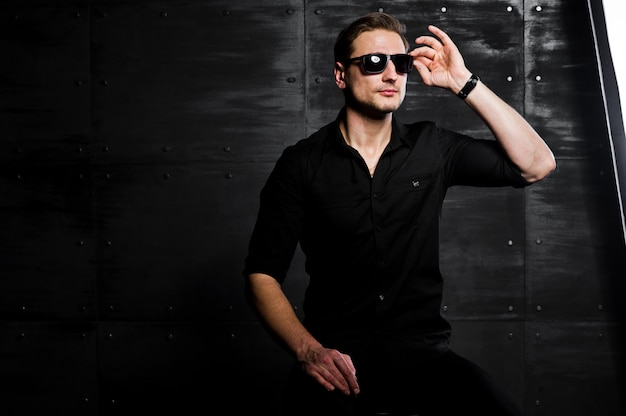 Portrait of stylish man wear on black shirt and glasses against steel wall.