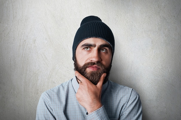 Portrait of stylish man with thick black beard wearing black cap and casual checked shirt