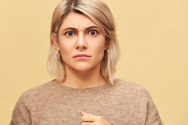 Portrait of stylish moody angry young caucasian woman wearing facial piercing and warm sweater frowning eyebrows being in bad mood, demonstrating her disapproval and discontent. negative emotions