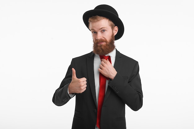 Portrait of stylish redhead young man with trimmed long beard posing in fashionable elegant clothes, showing thumbs up as sign of approval, going to buy this suit and hat