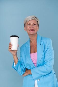 Ritratto di donna senior alla moda che tiene una tazza di caffè