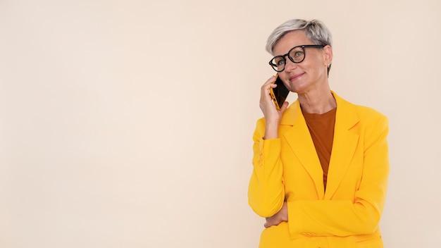 Ritratto di donna anziana alla moda che parla al telefono
