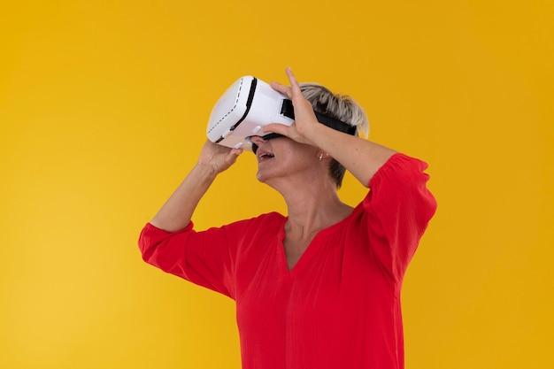 Ritratto di donna anziana alla moda che utilizza occhiali per realtà virtuale