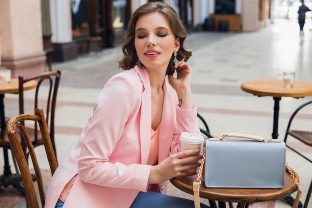 Ritratto di elegante sensuale signora seduta al tavolo bevendo caffè in giacca rosa tendenza stile estivo, borsa blu, accessori, street style, moda donna